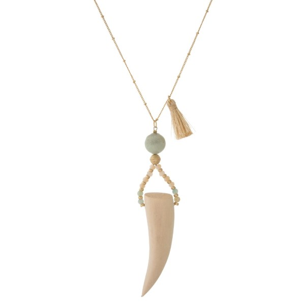 """Gold tone necklace with tassel detail, natural stone accents, and a horn pendant. Approximately 32"""" in length."""