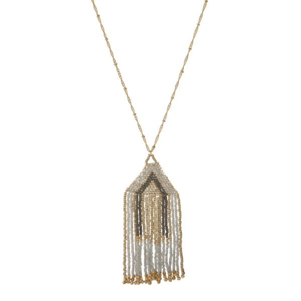 """Gold tone necklace with a metallic beaded pendant. Approximately 32"""" in length."""