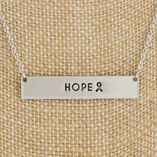 "Dainty tone necklace with a bar pendant, stamped with ""Hope"". Approximately 16"" in length."