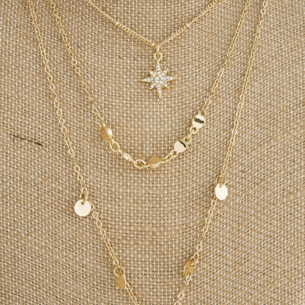 """Layered necklace with circle and starburst charms. Approximately 16""""-20"""" in length."""