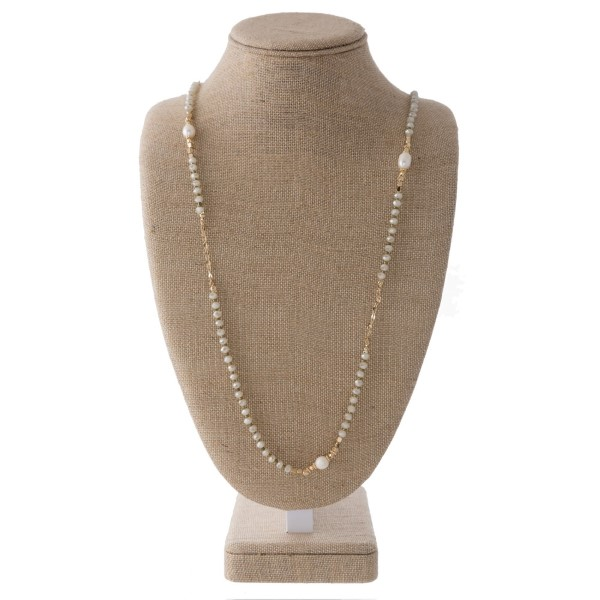 "Long gold tone necklace with pearl and faceted bead accents. Approximately 32"" in length."