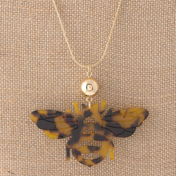 """Gold tone adjustable chain necklace with acetate bee shape pendant. Approximately 22"""" in length."""