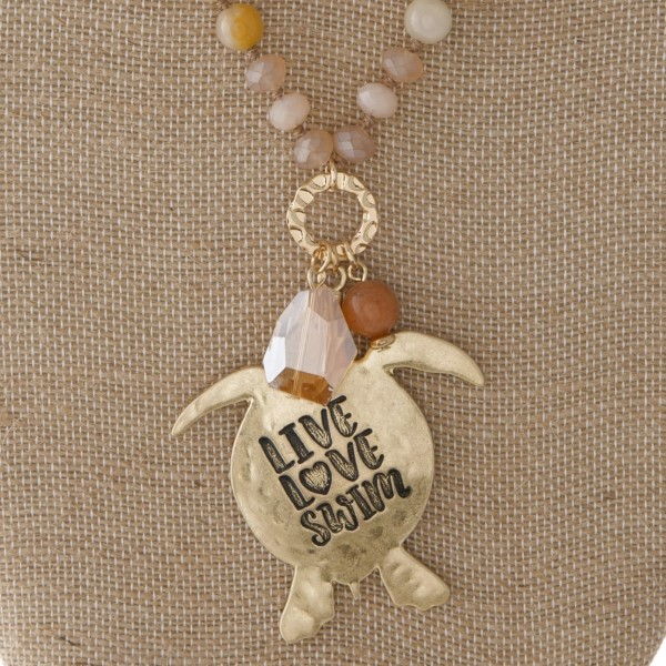 "Long necklace with faceted and natural stone beads and a turtle pendant. Approximately 32"" in length with a 2"" pendant."