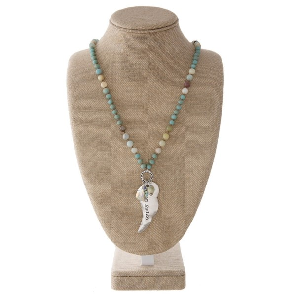 """Long necklace with faceted and natural stone beads and a wing pendant. Approximately 32"""" in length with a 2"""" pendant."""