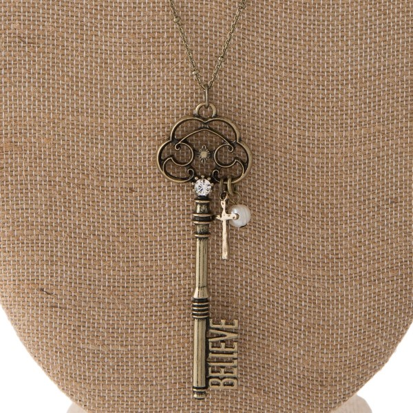 """Long necklace with key pendant with Believe cutout. Approximately 30"""" in length with a 3"""" pendant."""