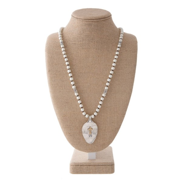 """Long pearl necklace with spoon pendant stamped with Lord's Prayer. Approximately 30"""" in length with a 2"""" spoon."""