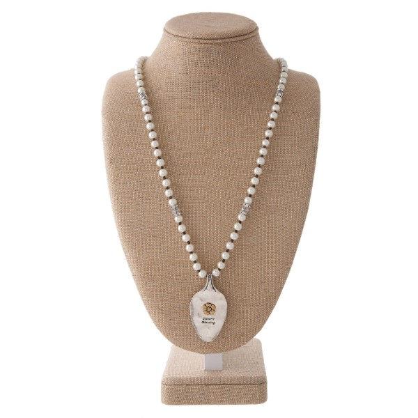 "Long pearl necklace with spoon pendant stamped with Sister's Blessing. Approximately 30"" in length with a 2"" spoon."