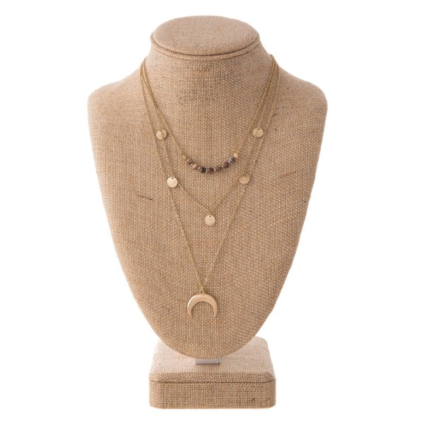"Gold tone layered necklace with natural stone, flat gold beads, and horn pendant. Approximately 16""-24"" in length."