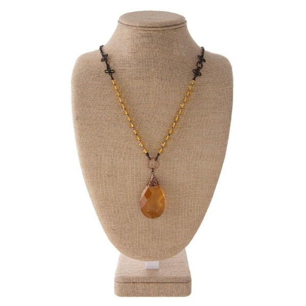 """Long necklace with faceted beads and crystal pendant. Approximately 28"""" in length."""