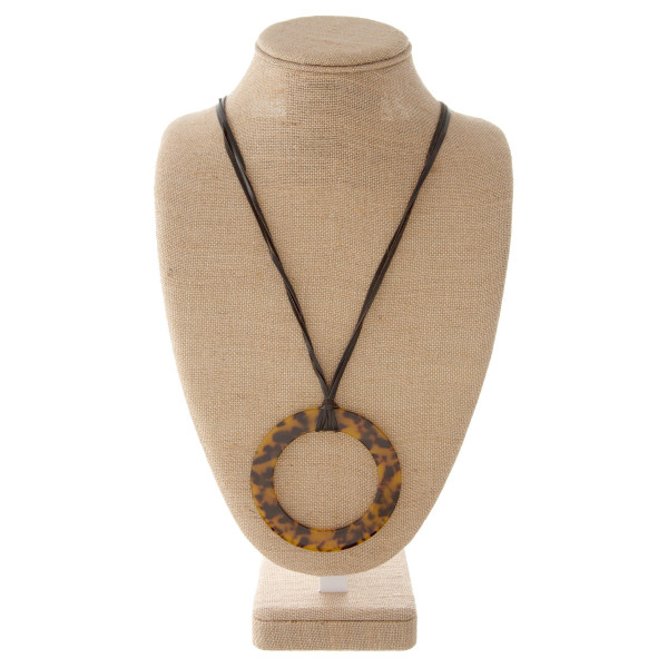 "Faux leather cord necklace with acetate circle pendant. Approximately 34"" in length with a 4"" pendant."