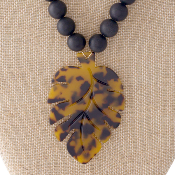 "Adjustable gold tone necklace with acetate palm leaf pendant. Approximately 24"" in length."