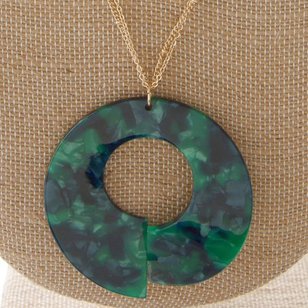 """Long gold tone necklace with acetate circle pendant. Approximately 30"""" in length."""