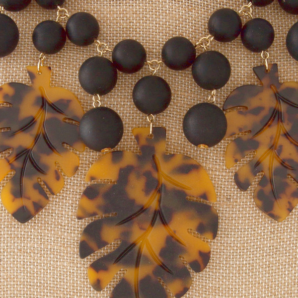 """Short statement necklace with acetate palm leaves. Approximately 20"""" in length."""