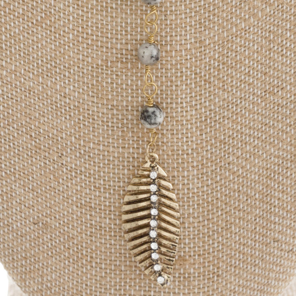 "Natural stone necklace with metal feather charm. Approximately 16"" with a 5"" Y."