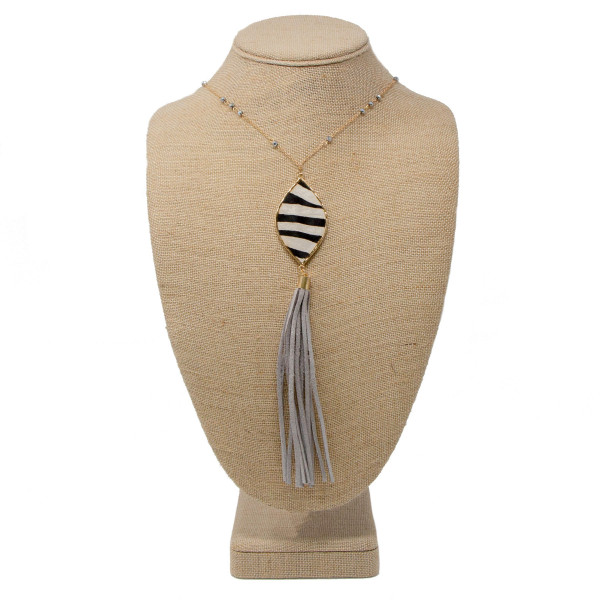 """Long metal necklace with animal print pendant and faux leather tassel. Approximately 32"""" in length with a 2"""" pendant and 4"""" tassel."""