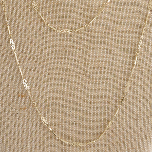 "Metal layered necklace with filigree details. Approximately 18-28"" in length."