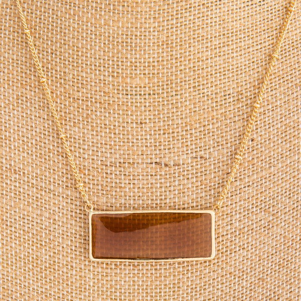 "Long gold metal necklace with acetate rectangle pendant. Approximate 14"" in length."