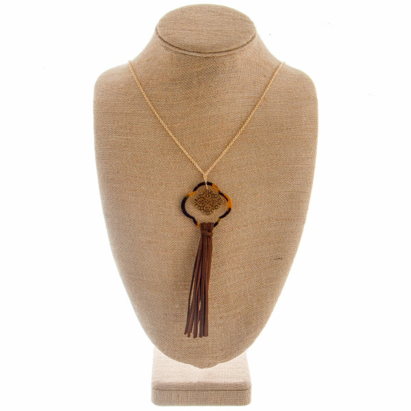 """Long metal necklace featuring a open clover with filigree detail and tassel. Approximate 42"""" in length with a 5.5"""" pendant."""
