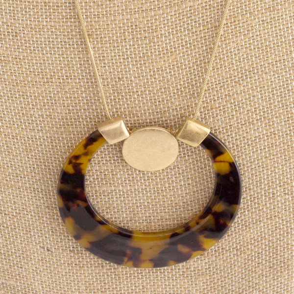 Long gold necklace with acetate pendant.