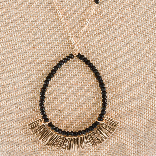 "Gorgeous drop metal necklace with beaded detail. Approximate 36"" in length and 2.5 in pendant."