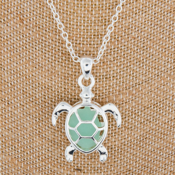 "Beautiful long metal neck with caged ""Turtle"" pendant with natural stone. Approximate 18"" in length with 1"" pendant."