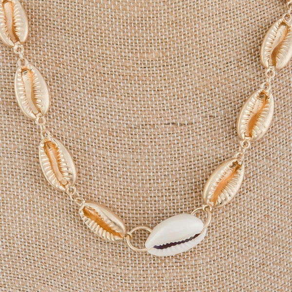 "Gold and natural medium length metal puka shell beaded necklace. Approximately 18"" in length."