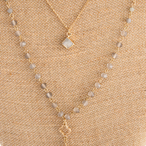 "Long gold beaded necklace with pendant and natural stone charms. Approximate 34"" in length with 2.5"" pendant."