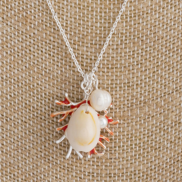 "Long metal necklace featuring a coral detail, puka shell, and pearl accents. Approximately 18"" in length."