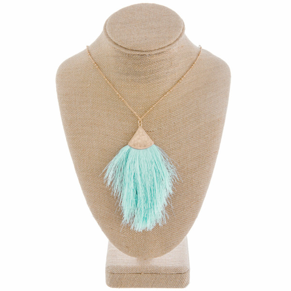 "Long gold metal necklace featuring a mint tassel pendant. Pendant approximately 4"". Approximately 38"" in length overall."
