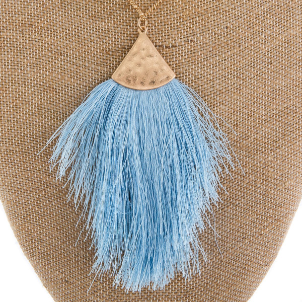 """Long gold metal necklace featuring a light blue tassel pendant. Pendant approximately 4"""". Approximately 38"""" in length overall."""
