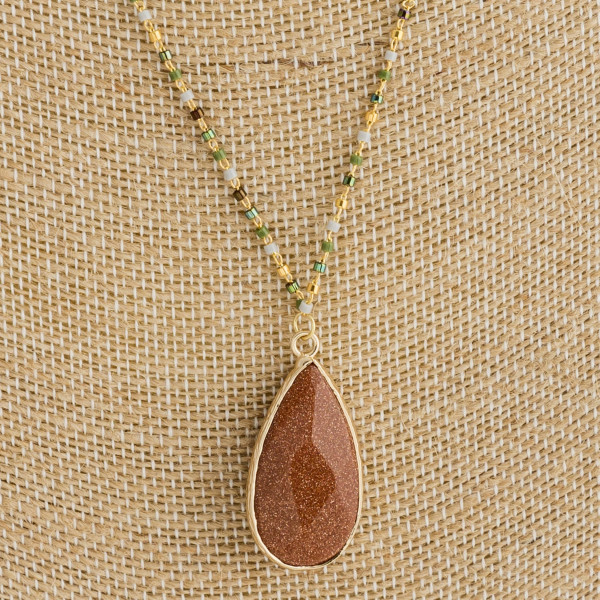 "Long beaded necklace with natural stone pendant. Approximate 16"" in length with 1"" pendant."