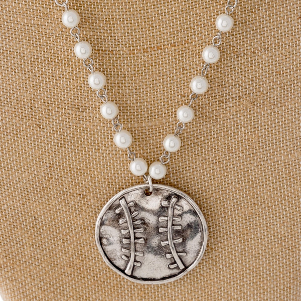 "Beaded chain necklace featuring a metal softball/baseball pendant with pearl bead details and silver accents. Pendant approximately 1.5"". Approximately 30"" in length overall."