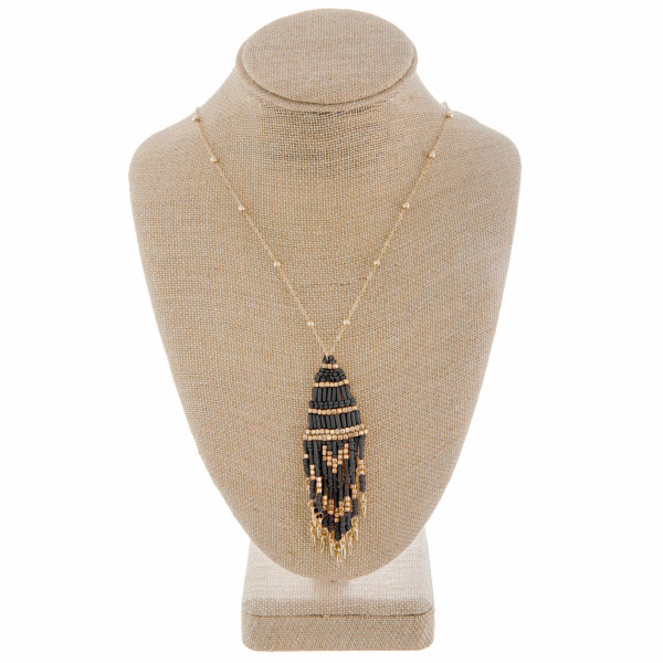 """Long metal necklace with beaded tassel. Approximate 36"""" in length."""