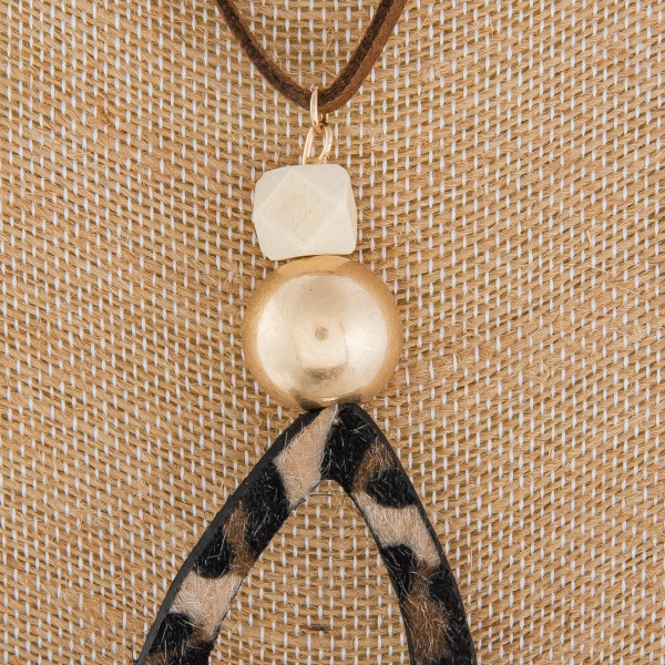 """Long leather necklace with beads and animal print drop pendant. Approximate 22"""" in length."""