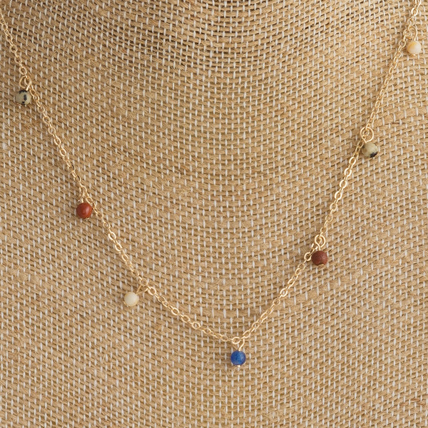"Dainty metal necklace featuring beaded accents. Approximately 14"" in length."