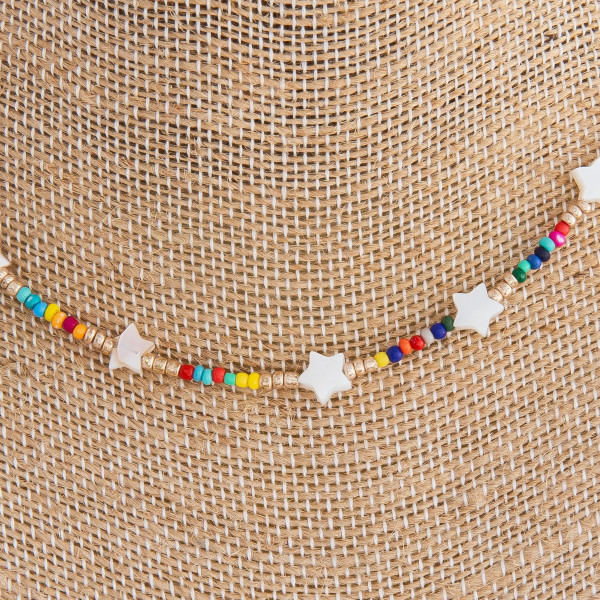 "Multicolor beaded necklace featuring gold and star accents. Approximately 16"" in length."