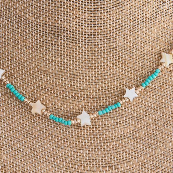 "Turquoise beaded necklace featuring gold and star accents. Approximately 16"" in length."