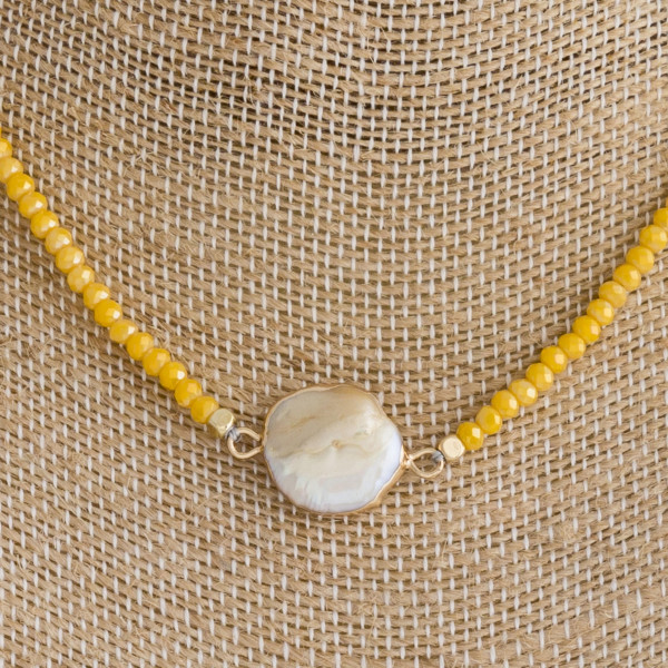 "Yellow beaded necklace featuring mother of pearl detail and a lobster clasp closure. Approximately 16"" in length."