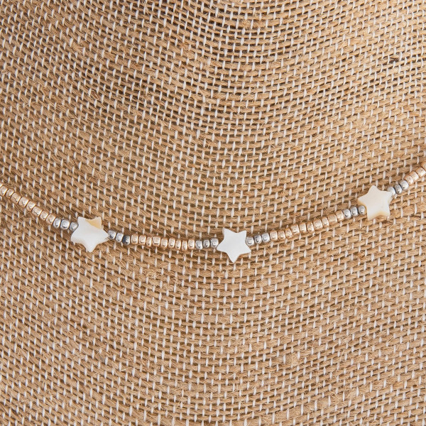 "Gold beaded necklace featuring silver star accents. Approximately 16"" in length."