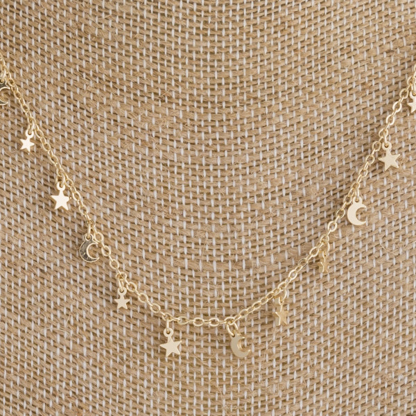 "Gold metal necklace featuring gold moon and star accents. Approximately 16"" in length."