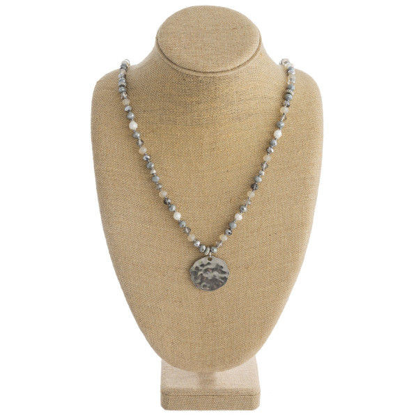 """Long beaded necklace featuring a circular metal pendant with pearl accents. Pendant approximately 1.5"""" in diameter. Approximately 38"""" in length overall."""