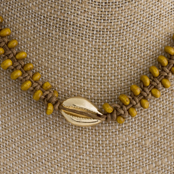 "Short rope braided necklace with wood bead and seashell details. Approximate 10"" in length."