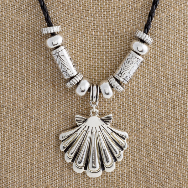 """Long leather braided necklace with clamshell pendant. Approximate 17"""" in length."""