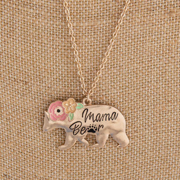 "Long metal necklace featuring ""mama bear"" pendant with flower detail. Approximately 30"" in length."