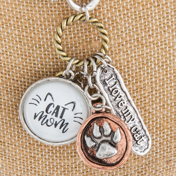 "Long metal necklace featuring multi ""Cat Mom"" hanging charms with a pearl accent and a toggle clasp. Pendant approximately 2"". Approximately 36"" in length."