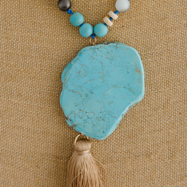 """Long beaded necklace featuring natural stone, acrylic and wood bead details with natural stone pendant and a tassel accent. Pendant approximately 7"""". Approximately 46"""" in length overall"""