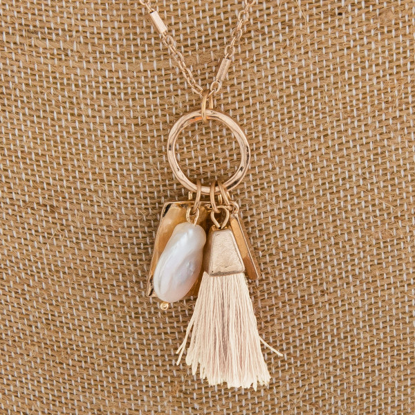 "Long metal necklace with small tassel and pearl charms. Approximate 32"" in length."