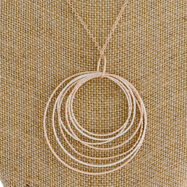 "Long rose gold chain necklace featuring a circular pendant with silver accents. Measures approximately 36"" in length."