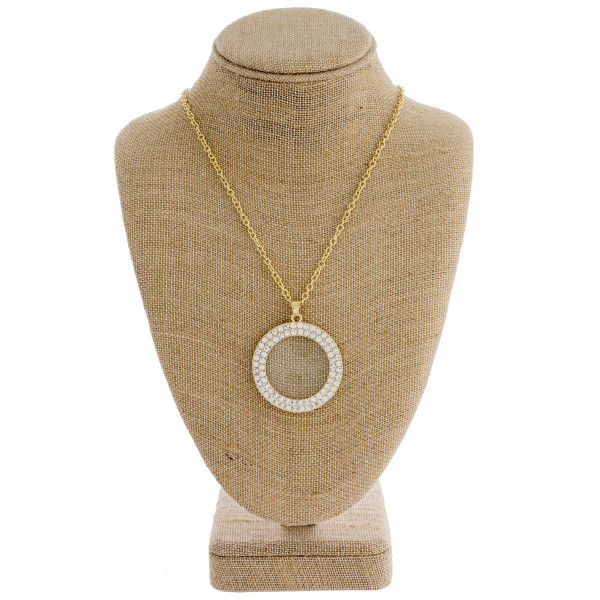 "Long gold necklace featuring a circular rhinestone pendant. Approximately 36"" in length. Pendant is approximately 1.5"" in diameter."