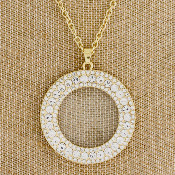 "Long gold necklace featuring a circular rhinestone pendant. Approximately 36"" in length. Pendant is approximately 2"" in diameter."